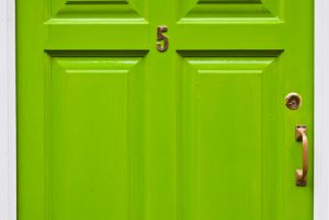 green typical residential house door in Ireland (number 5, golden lock and handle)