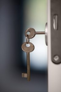 Close-up shot of keys in the lock of open door. One key is in lock another hanging on the ring
