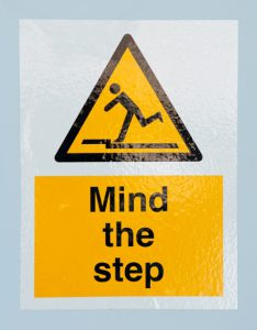 mind the step caution sign on a blue wall background